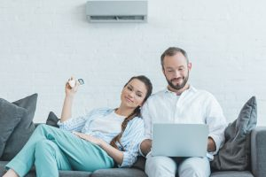 Couple sitting on couch next to a wall-mounted ductless unit